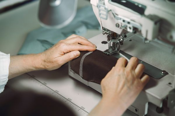 Old woman use sewing machine. Designes sew cloth. Brunette in studio.
